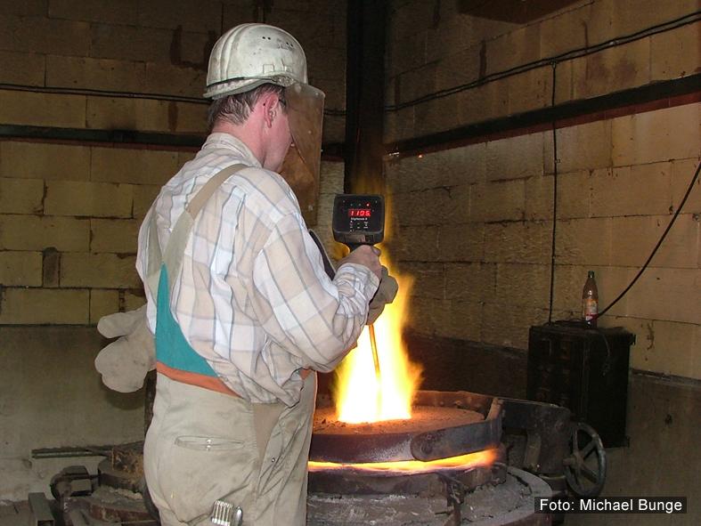 Bruder Michael bei der Temperaturprüfung der flüssigen Bronze